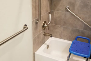 Three Grab Bars Installed In Bathroom Shower With Blue Shower Chair