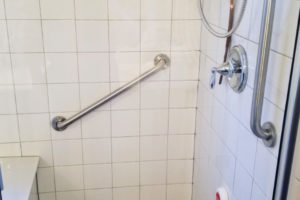 Two Grab Bars Installed In Tiled Walk In Shower With Bench