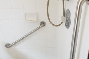 Two Grab Bars Installed On White Tile Shower With Shower Chair