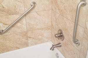 Two Stainless Steel Grab Bars Installed On Tiled Walls Over Bathtub